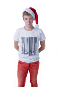 holiday portrait with a young caucasian male wearing a santa hat over a white backgroundの写真素材 [FYI00786415]