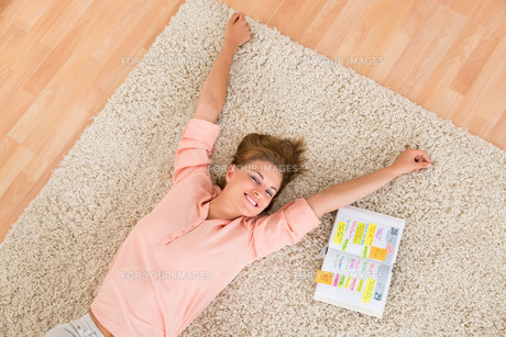 Woman With Diary Lying On Carpetの写真素材 [FYI00786448]