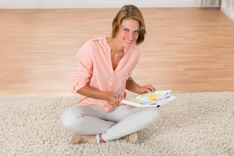 Woman With Diary Sitting On Carpetの写真素材 [FYI00786452]