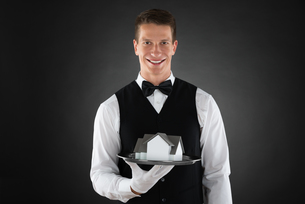Waiter Holding Tray With Miniature Houseの写真素材 [FYI00786507]