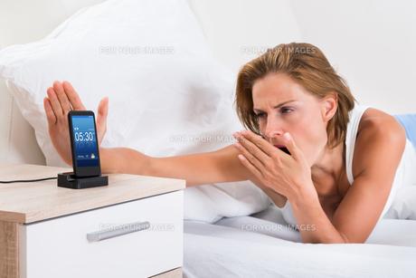 Woman Yawning While Snoozing Alarmの写真素材 [FYI00786518]