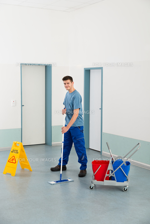 Male Worker With Cleaning Equipments Mopping Floorの写真素材 [FYI00786520]