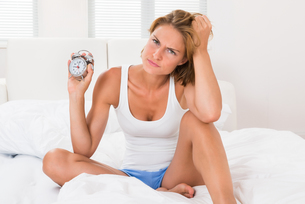 Woman Sitting On Bed With Alarm Clockの写真素材 [FYI00786521]