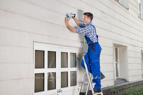 Technician Fixing Cctv Camera On Wallの素材 [FYI00786525]