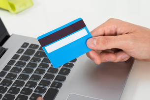 Person Hands With Credit Card Over Laptop Keypadの写真素材 [FYI00786526]