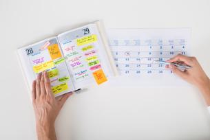 Person Hands Highlighting Date On Calendarの写真素材 [FYI00786531]