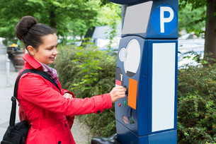 Woman Inserting Coin In Parking Meterの写真素材 [FYI00786545]