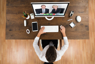 Businessman Videochatting With Senior Colleagues On Computerの写真素材 [FYI00786549]