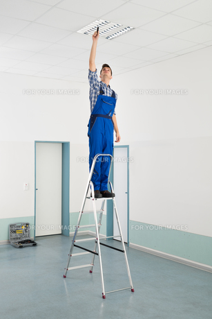 Electrician Installing Ceiling Lightの写真素材 [FYI00786564]