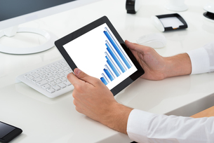 Businessperson Analyzing Graph On Digital Tabletの写真素材 [FYI00786571]