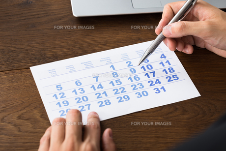 Businessperson Holding Pen Over Calendarの写真素材 [FYI00786604]