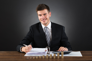 Businessman Doing Accounting At Deskの写真素材 [FYI00786611]