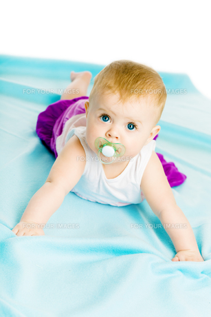 baby girl with pacifier crawling on the blue coverletの写真素材 [FYI00786623]