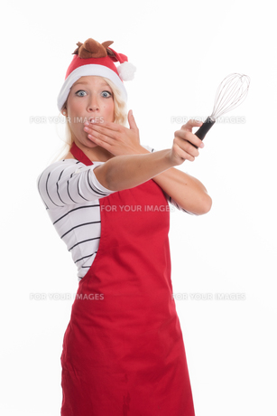 christmas woman in apron showing a beater and is scaredの素材 [FYI00787409]