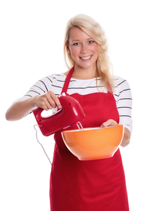 woman in apron stirred with a mixer in a bowlの写真素材 [FYI00787421]