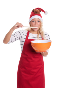 christmas woman in apron with mixing bowl and wooden spoonの写真素材 [FYI00787425]