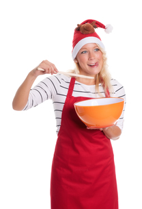 christmas woman in apron with mixing bowl and wooden spoonの写真素材 [FYI00787438]