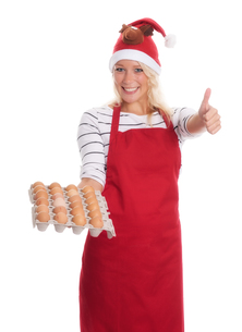 woman with santa hat and apron holding a palette eggsの写真素材 [FYI00787439]