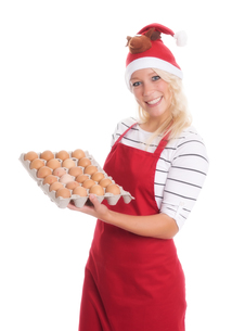 woman with santa hat and apron holding a palette eggsの写真素材 [FYI00787445]