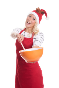 christmas woman in apron with mixing bowl and wooden spoonの写真素材 [FYI00787448]