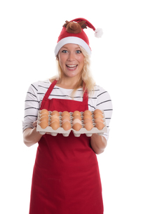 woman with santa hat and apron holding a palette eggsの写真素材 [FYI00787449]