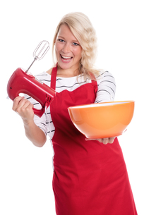 woman in apron stirred with a mixer in a bowlの写真素材 [FYI00787452]