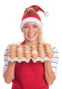 woman with santa hat and apron holding a palette eggsの写真素材 [FYI00787454]