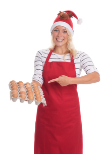 woman with santa hat and apron holding a palette eggsの写真素材 [FYI00787470]