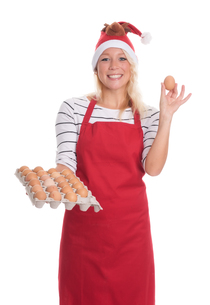 woman with santa hat and apron holding a palette eggsの写真素材 [FYI00787471]