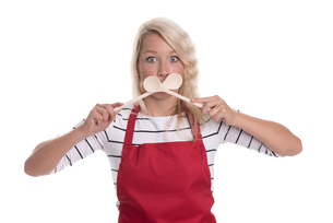 housewife in apron holding up wooden spoon to her mouthの写真素材 [FYI00787476]