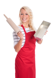 young woman holding a baking pan and rolling pinの素材 [FYI00787495]