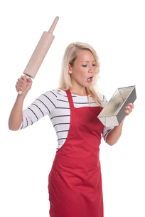 astonished housewife with baking pan and rolling pinの素材 [FYI00787509]