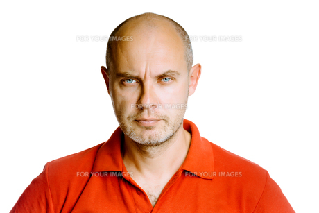 Unshaven fearsome middle-aged man in a red T-shirt. Studio. isolatedの写真素材 [FYI00787627]