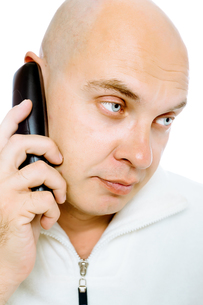 Bald, blue-eyed man with a telephone. Studio. isolatedの写真素材 [FYI00787630]