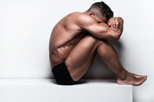 Muscular Man Sitting with Face Hidden Folded Armsの写真素材 [FYI00787947]