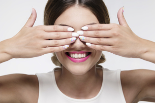 beauty woman smiling hiding her eyes with gel nailsの写真素材 [FYI00787971]