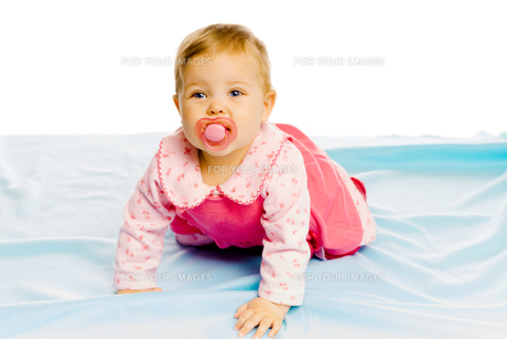 baby girl with pacifier crawling on the blue coverlet. Studioの写真素材 [FYI00788582]