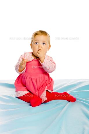 Beautiful baby sitting on a blue blanket. Studioの写真素材 [FYI00788598]
