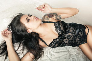 brunette girl in bed with cigaretteの写真素材 [FYI00788820]