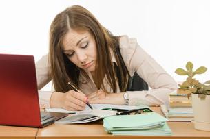 Tired teacher checks students notebooksの写真素材 [FYI00788870]