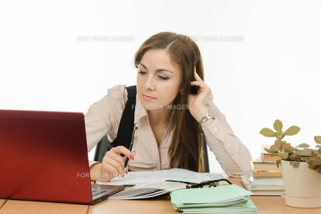 The teacher looks intently at a laptopの写真素材 [FYI00788882]