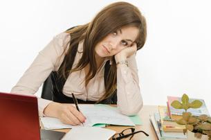Tired teacher checks students notebooksの写真素材 [FYI00788921]