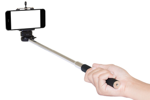 hand holding phone selfie stick isolated with clipping pathの写真素材 [FYI00789065]