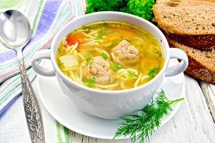 Soup with meatballs and noodles in bowl on boardの写真素材 [FYI00789227]
