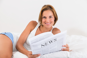 Woman In Bed With Newspaperの写真素材 [FYI00789509]