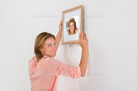 Happy Woman Putting Picture Frame On Wallの写真素材 [FYI00789513]