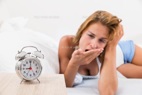 Woman With Alarm Clock On Nightstandの写真素材 [FYI00789534]