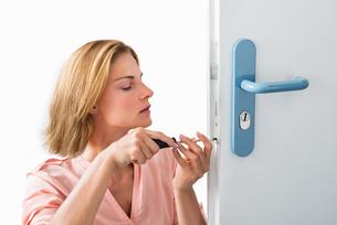 Young Woman Fixing Doorの写真素材 [FYI00789541]