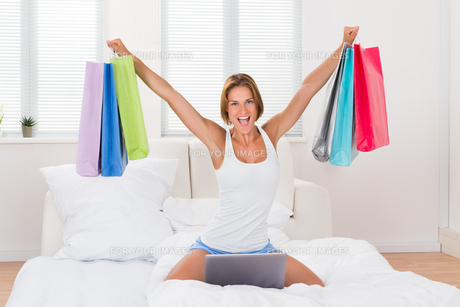 Excited Woman Holding Shopping Bagsの写真素材 [FYI00789542]