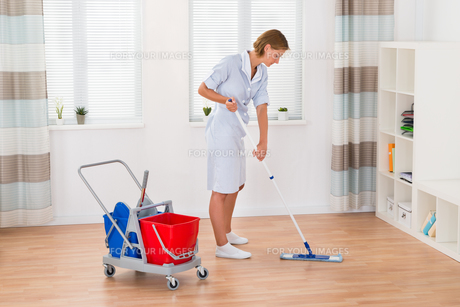 Female Housekeeper Cleaning Floor With Mopの写真素材 [FYI00789549]
